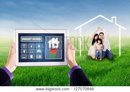 Male hands holding smart house controller apps on the tablet with happy family making a symbol house on the meadow