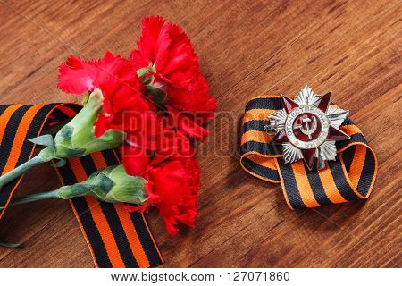 Order Of The Patriotic War 1St Class And Two Red Carnations. Victory Day. 9 May. Selective Focus Ima