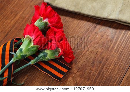 Three Red Flower And Paper And Soldier's Forage Cap On A Wooden Background. Selective Focus Image