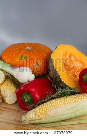 Organic pumpkin squash with fresh vegetables for soup: corn red peppers scallion rosemary and ginger over a wood table on natural environment.