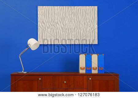 Wooden chest of drawers on blue wall background