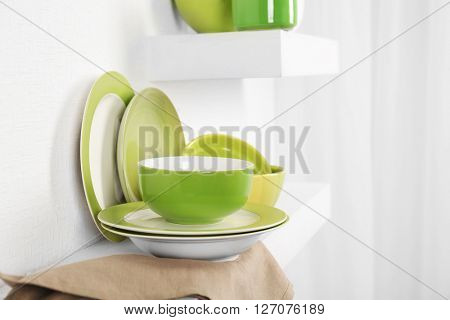 Set of tableware with napkin on shelf against white wall background
