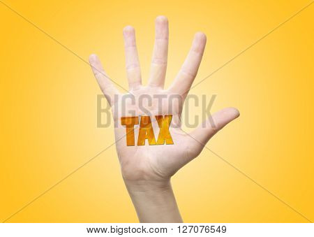 Tax concept. Woman's hand with Tax sign, on yellow background