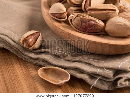 close up of pistachios on a wooden spoon
