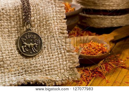 Medallion with the sign of Aries on sackcloth and saffron in a wooden spoon