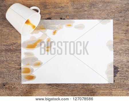 coffee spilled out from white cup on white paper and wooden background