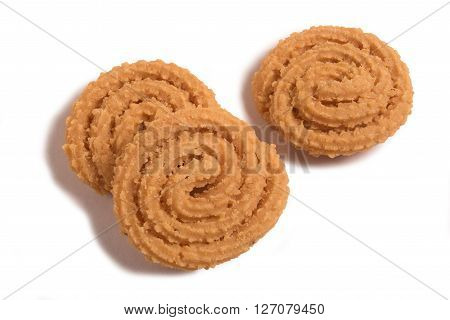Murukku - savoury a crunchy South Indian snack. Made os rice flour black gram sesame cumin seeds and salt. the kneaded dough is shaped into spiral shapes by hand. Deep fried in vegetable oil.