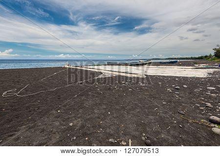 Saint-Paul Reunion Island France - December 24 2015: Fishing nets drying on the black beach in Saint Paul on the island of La Reunion (France) in the Indian ocean.