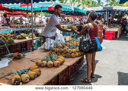 Saint-Paul Reunion Island France - December 24 2015: Vendor fresh fruit pineapple on a local market in Saint Paul on the island of La Reunion (France) in the Indian ocean.