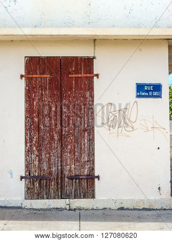 A wooden old door and plate with name of the street rue du General de Gaulle in Saint Paul on the island of La Reunion (France) in the Indian ocean.