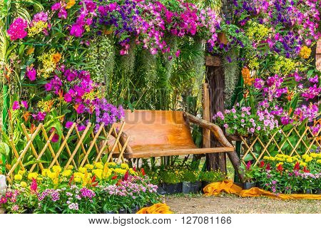 Wood Chair In The Flowers Garden.