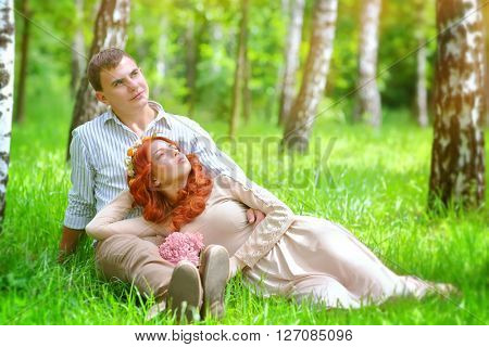 Portrait of a gentle young couple relaxing in a fresh green spring park, sitting on a field between birch trees, enjoying wedding day