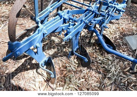 Detail of vintage tilling machinery for the agriculture industry with blue metal, rusted wheel, and blades.