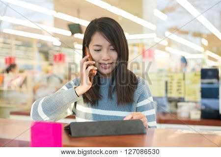 Woman use of tablet pc and talk to mobile phone