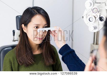 Woman checking vision with tonometer at eye clinic