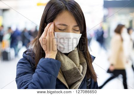 Woman suffer from headache and wearing face mask