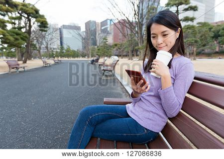 Woman drinking coffee and use of mobile phone