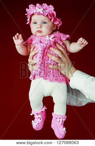 father holding his four months old baby, against red studio background