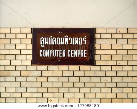 A brown computer centre sign mounted on a brick pattern wall.