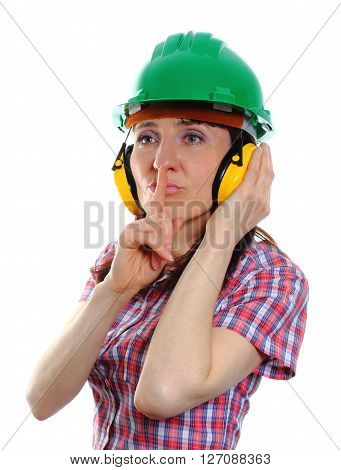 Female construction worker wearing green helmet and protective headphones holding finger to lips and showing silence sign safety at work and ear protection. White background
