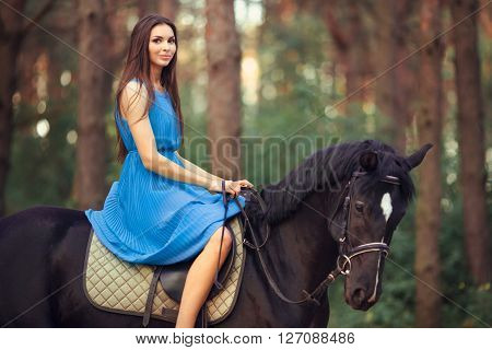 Portriat of smiling young beautiful brunette girl in blue dress ride on the black horse in forest