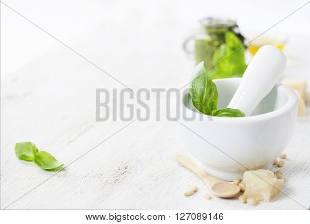 Ceramic Mortar with Pestle and Pesto ingredients over white