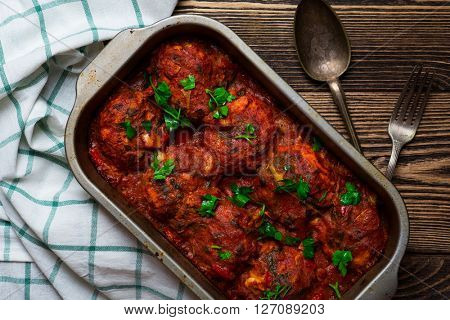 Delicious meatballs in a spicy tomato sauce on wooden background