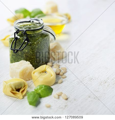 Homemade raw Italian tortellini with pesto on rustic wooden background