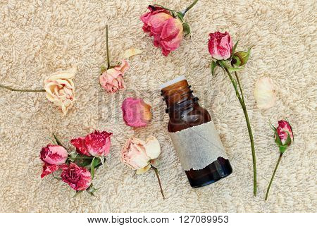 Herbal relaxation.Rose essential oil in bottle, scattered dried rose flowers, bathroom soft towel.