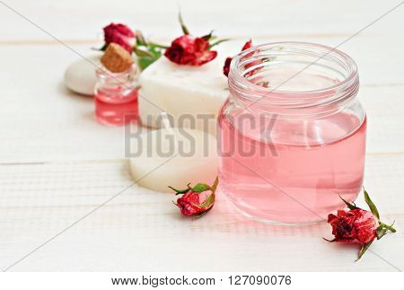 Rose essence. Rose water in jar, dried roses, candle, relaxing aromatherapy. Soft focus, soft light.