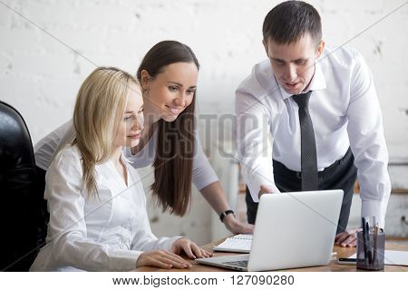 Teamwork concept. Group of three smiling young people working on project at office desk. Business team in formal wear using computer while discussing cooperative work