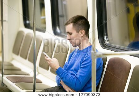Young Man Commuting By Subway Train