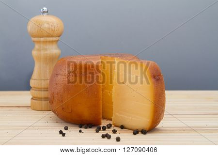 Cheese Wheel And Slice With Wooden Peppermill With Peppercorns