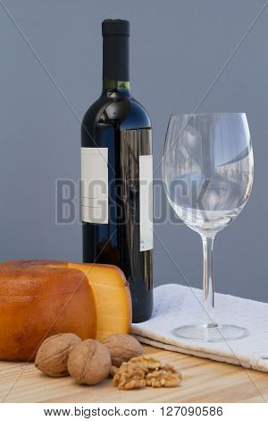 Cheese Wheel And Slice With Nuts And Malbec Wine Bottle