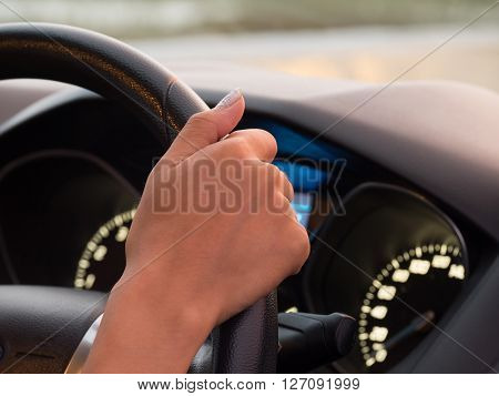 Girl one hand driving car showing meters