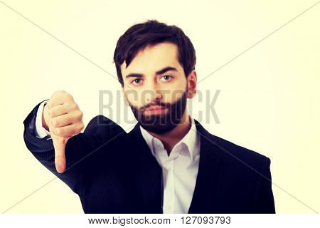 Unhappy businessman with thumbs down gesture.