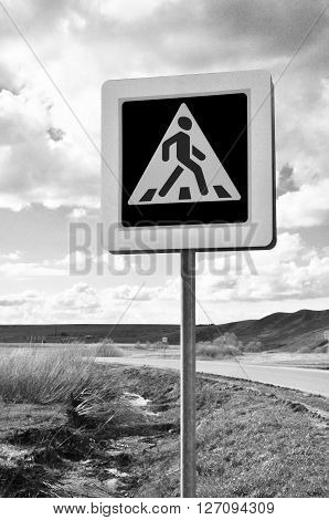 A pedestrian crossing sign on old road. Photo traffic sign on a metal pole.