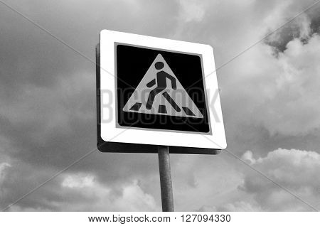 A pedestrian crossing sign. Photo traffic sign on a metal pole.