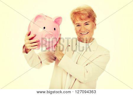 Smile elderly woman holding piggy bank