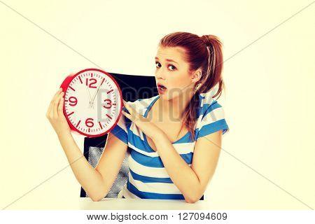Young shocked teenage woman looking at clock