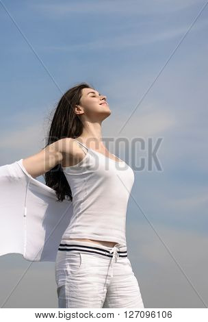 Girl Breathes In Fresh Air On A Blue Sky Background.
