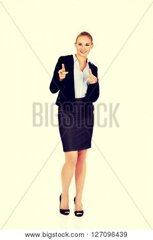 Young business woman making a gun gesture