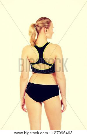 Back view of young athletic woman in sports underwear