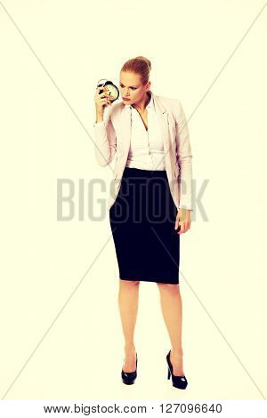 Shocked business woman listening to alarm clock