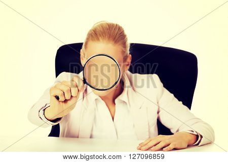 Business woman sitting behind the desk and looking into a magnifying glass