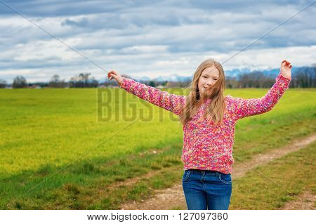 Adorable little girl of 8 years old playing outdoors, wearing colorful warm pullover, arms up wide open