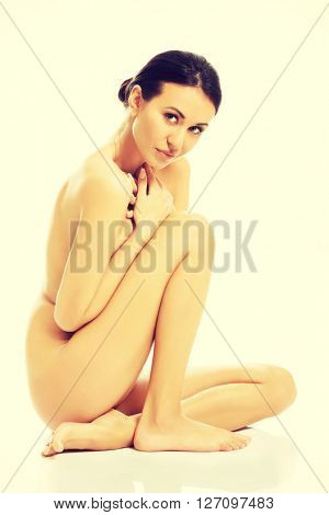 Topless woman sitting with knee close to chest
