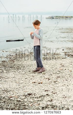 Adorable little girl of 8-9 years old playing by the lake, wearing grey trousers and long cardigan