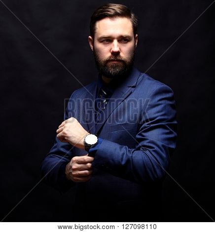 Cool young businessman standing on dark background