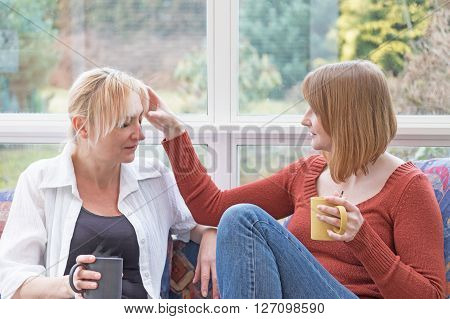 Middle aged woman and a young woman are chatting together sitting on the sofa in the conservatory. Young woman is touching the head of the other.